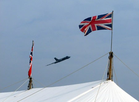 A Vulcan bomber flies over the flag-bedecked 'Spitfire Café' refreshment tent at Goodwood Revival