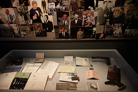 Showcase of personal effects sits in front of a collage of James Bond images