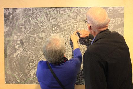 Visitors exploring aerial photograph, Navigating Norman Creek, Museum of Brisbane, 2015