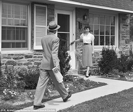 An immaculate housewife waits at the door to greet her husband