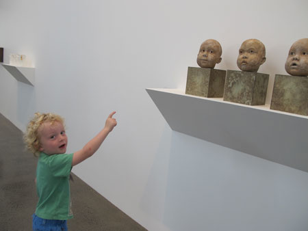 A pre-school child contemplating a series of sculptures in an exhibition of ceramics at Te Uru Waitakere Contemporary Gallery, Auckland (2015).