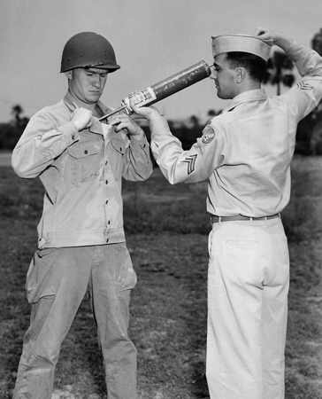 A US soldier is demonstrating DDT hand-spraying equipment while applying the insecticide