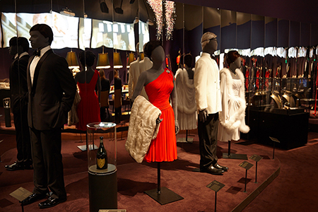 Display of costumes in the 'Casino' exhibit, featuring the red dress worn by Eunice Gayson as Sylvia Trench in Dr. No
