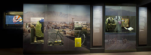 Display case in the gallery with one showing a bicycle that has an IED concealed on it