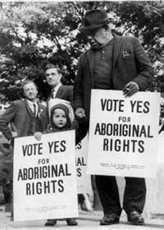 Image of Bill Onus and child holding Aboriginal rights posters
