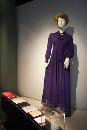 The 'Florence' dress designed by Hijab House, with a multimedia label strip in the foreground that includes a mix of labels written by the Muslim women featured in the exhibition, children's labels, creative process material and touch samples