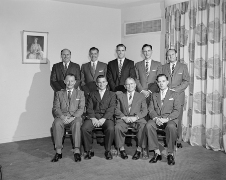 Staff photograph of postal inspectors with image of the Queen on the wall.